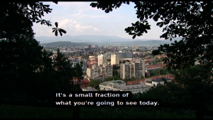 "A screen shot from a broadcast, displaying some buildings, and machine-translated subtitles in English, which states ""It's a small fraction of what you're going to see today."""