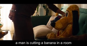 Screenshot from the Disney film 'Saving Mr Banks'. A woman, standing, reaches out her arm to lift a Pluto toy off a sofa.