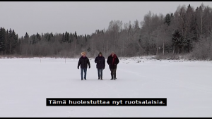 "Screenshot from a television documentary of a wintry scene where three people walk towards the camera at a middle distance in a snow-covered open space with a forest in the background. There is a machine-translated subtitle in Finnish at the bottom of the screen that says: ""Tämä huolestuttaa nyt ruotsalaisia."" The English translation of the subtitle is ""This is now causing concern to Swedes."""